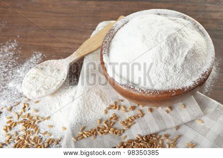 Whole flour with wheat on wooden table, closeup