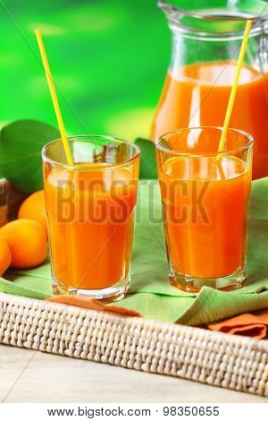 Glasses of apricots juice in wicker tray on green blurred background