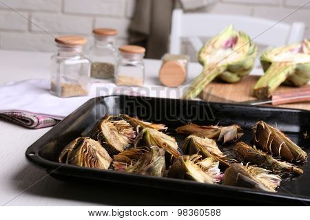 Roasted artichokes on pan, on kitchen table background
