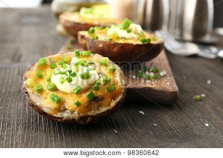 Baked potato with mayonnaise and chives on wooden cutting board, closeup