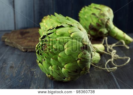 Artichokes on color wooden background