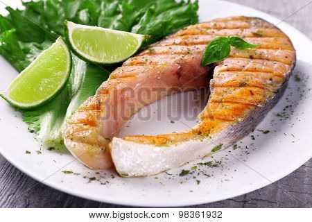 Tasty grilled salmon with lime and lettuce on table close up