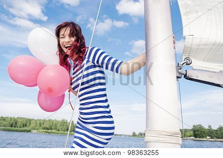 Attractive happy girl with balloons on a yacht at summer day