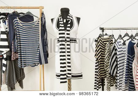 Dressing Closet With Striped Clothes Arranged On Hangers And A Black And White Outfit On A Mannequin