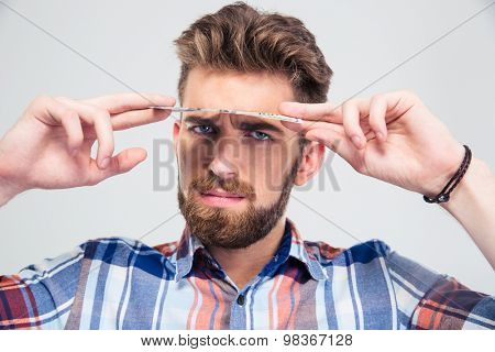 Man looking at camera from under dollar bill isolated on a white background
