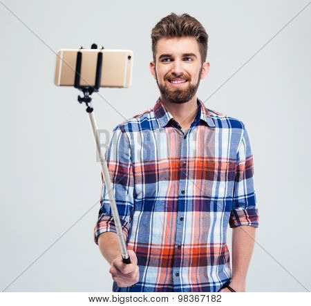 Portrait of a happy man with beard making selfie photo with stick isolated on a white background