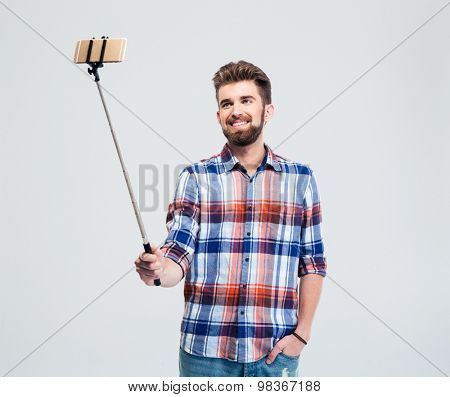 Happy casual man making selfie photo with stick isolated on a white background