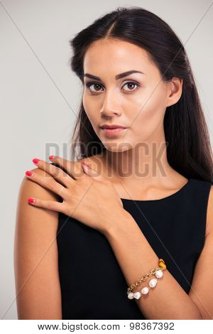Jewerly concept. Portrait of a pretty female model in black dress posing isolated on a white background. Looking at camera