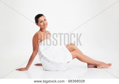 Portrait of attractive woman in towel sitting on the floor isolated on a white background. Looking at camera