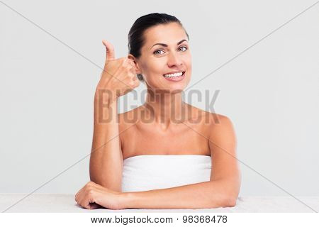 Smiling woman in towel sitting at the table and showing thumb up isoalted on a white background. Looking at camera