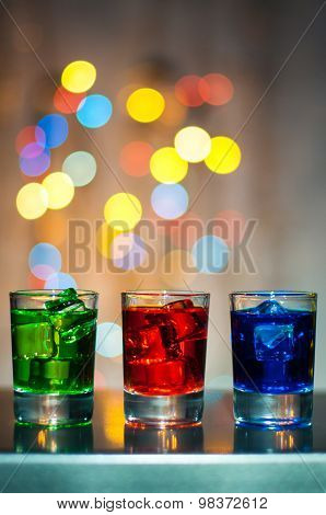 Three shot glasses with cocktail or liquor. Happy party background