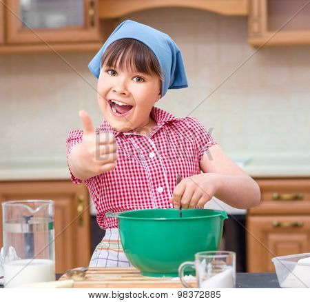 Girl is cooking in kitchen and showing thumb up sign, indoor shoot