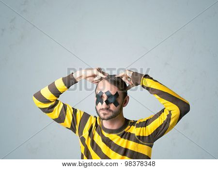 Young man with taped eye. Isolated on gray background