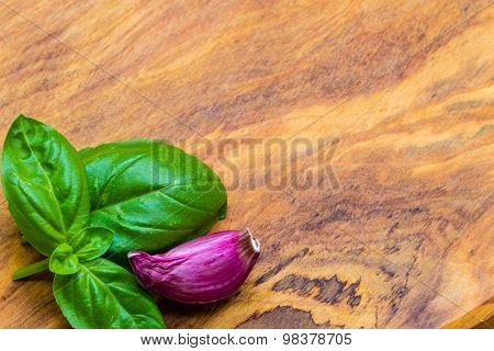 Garlic Clove And Basil Leaves On Wooden Table Background