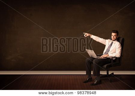 Businessman holding high tech laptop on brown background with copyspace