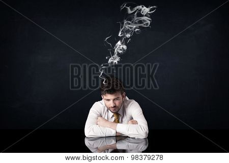 Young depressed businessman sitting with smoking head