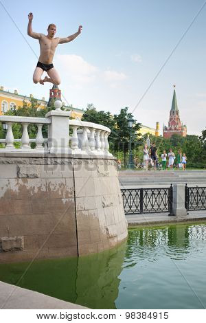 MOSCOW - AUG 12, 2014: A young man jumping in the water at the Manege Square