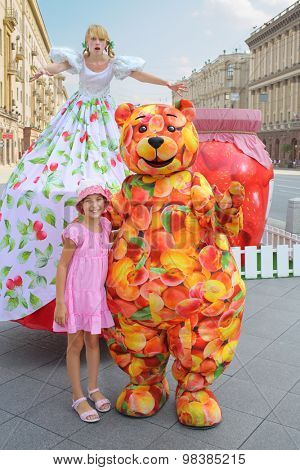 MOSCOW - AUG 12, 2014: Little girl beside the girl on stilts and bear in fruit suits in Moscow festival jam on Tverskaya Square