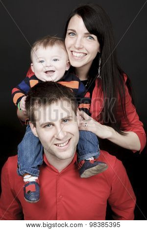 Happy family, father, mother and infant in front of a black back