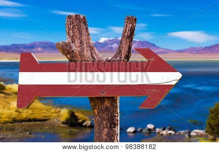 Latvia Flag wooden sign with a beautiful view on background