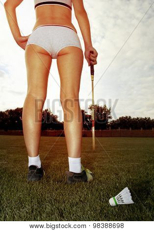 long legs of woman who plays badminton on grass