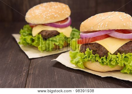 Cheeseburger On Buns With Succulent Beef On The Wooden Background