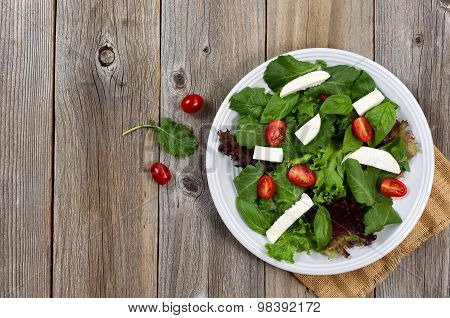 Healthy Green Salad On White Plate With Rustic Wooden Boards
