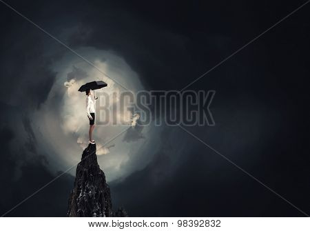 Young businesswoman with black umbrella standing on top
