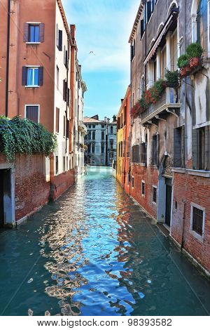 Eternal fantastic Venice. Narrow street - channel. In water the dark blue sky is reflected