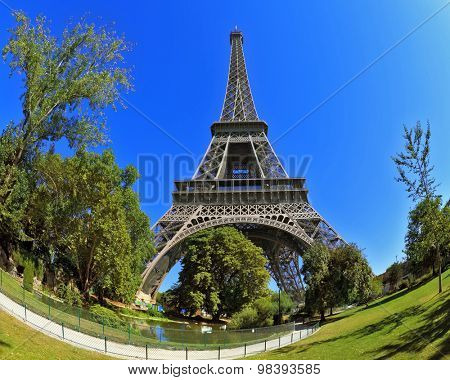Huge and beautiful Eiffel Tower. The picture was taken Fisheye lens. At the foot of the tower is designed park with paths and pond