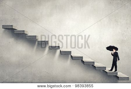 Businessman holding umbrella and waking on career ladder