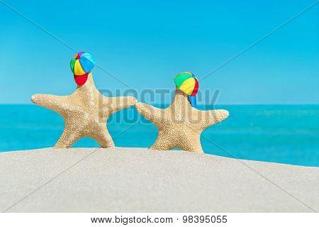 Sea-stars In Peaked Caps Walking At Sandy Sea Beach