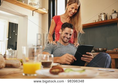 Happy Young Couple In Kitchen Using Tablet Pc