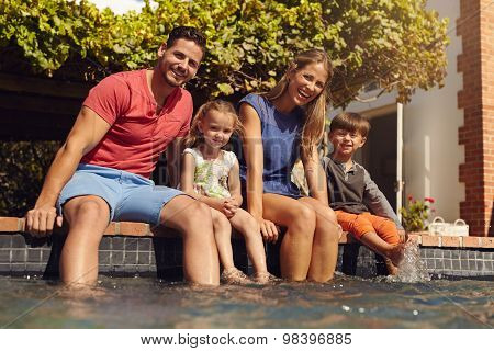 Family Sitting With Feet In Swimming Pool