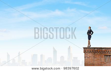 Confident pretty businesswoman standing on building top