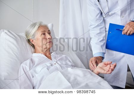 medicine, age, health care and people concept - doctor with clipboard visiting senior patient woman and checking her pulse at hospital ward