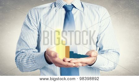 Close up of businessman holding decline graph in palm