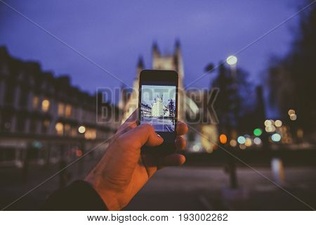BATH, UNITED KINGDOM - MARCH 8, 2017: Point of view of man taking photograph with the mobile phone smartphone of the illuminated cathedral Bath Abbey in Bath United Kingdom