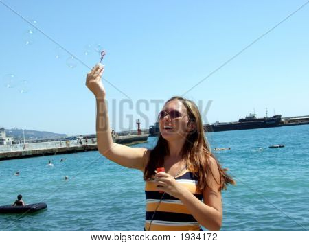 The Beautiful Girl Starts Up Soap Bubbles On Quay