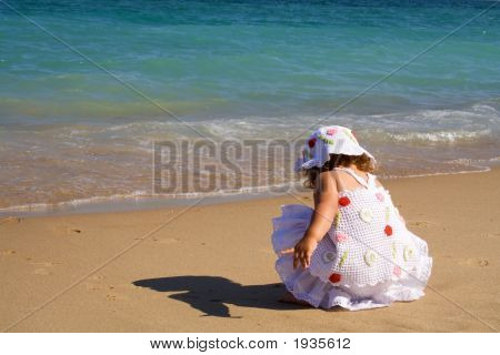 Little Girl Crouching On The Beach