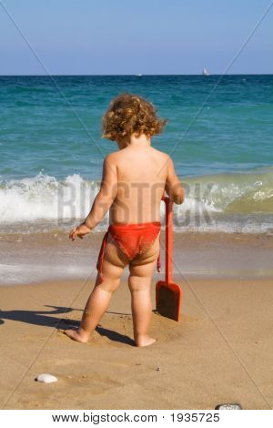 Little Girl With Toy Shovel On The Beach