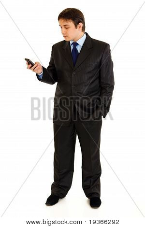 Full length portrait of businessman holding mobile in hand and looking on it isolated on white