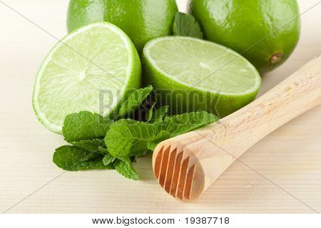 Mojito mix on wood table: lime, mint and muddler