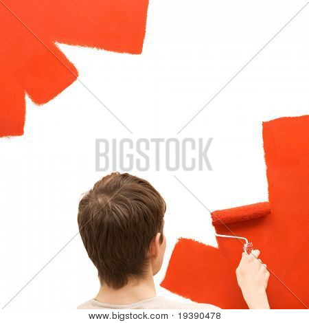 Young man paints the wall