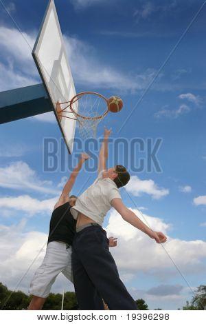 Teenagers play basketball