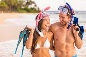 Happy couple laughing together beach fun on summer snorkel travel vacation healthy active lifestyle. poster