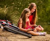 Bikes cycling kids. Girl recreation near bicycle into park. Children watch tablet pc. Girl in ecotou poster