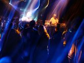 foto of night-club  - DJ spins music at crowded concert venue