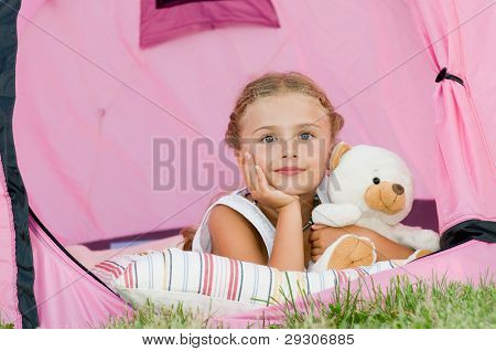 Camping in tent - cute girl on camp tent