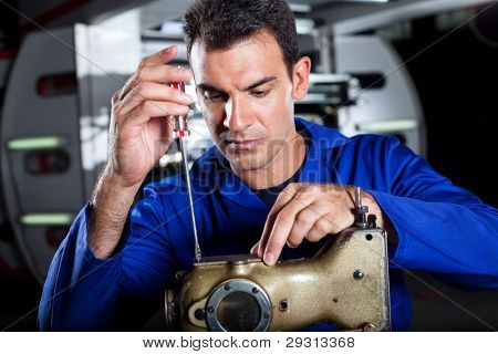 skilled mechanic repairing industrial sewing machine in factory